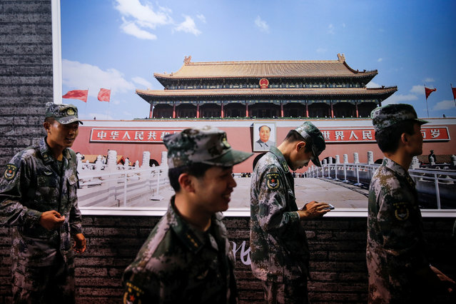 Soldiers of China's People's Liberation Army (PLA) walk past a poster of Tiananmen Square at an exhibition celebrating the 95th anniversary of the foundation of Communist Party of China in Shanghai, China, June 27, 2016. (Photo by Reuters/Stringer)