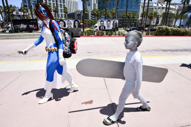 Dina Mills, left, and her son walk outside of the convention center on day 1 of the 2014 Comic-Con International Convention held Thursday, July 24, 2014 in San Diego. (Photo by Denis Poroy/Invision/AP Photo)
