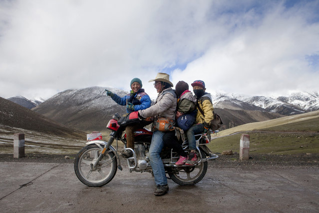 The family of Chu Tsering, 47, pose for a portrait on his motorbike while on their way to the harvest of the Cordyceps, also known as Caterpillar Fungus, on the mountains in the surroundings of Xiaosumang Township, on May 31st, 2016. (Photo by Giulia Marchi/The Washington Post)