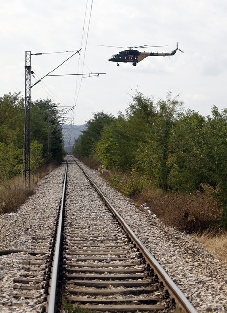 A police helicopter flies over railroad tracks near the border between Greece and Macedonia, near the southern Macedonian town of Gevgelija, Thursday, August 20, 2015. (Photo by Darko Vojinovic/AP Photo)