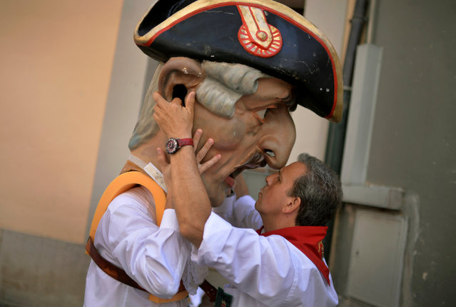"""An assistant helps a """"Kiliki"""", a Big Head, to dress at the San Fermin festival in Pamplona, northern Spain July 8, 2016. (Photo by Vincent West/Reuters)"""
