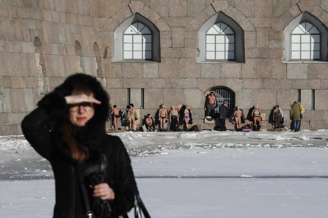 People take a sunbath near the Peter and Paul fortress on a sunny day in central St. Petersburg, Russia, 07 February 2020. The air temperature dropped to minus six degrees Celsius in Russia's second largest city. (Photo by Anatoly Maltsev/EPA/EFE)