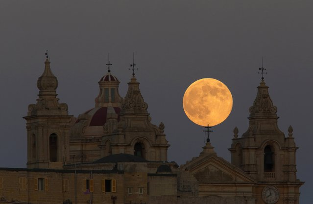The supermoon rises behind the cathedral in Mdina, Malta's ancient capital city, in the centre of the island, August 10, 2014. The astronomical event occurs when the moon is closest to the Earth in its orbit, making it appear much larger and brighter than usual. (Photo by Darrin Zammit Lupi/Reuters)