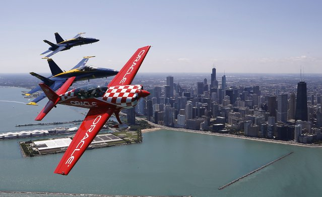 Sean Tucker pilots his plane along with two members of the U.S. Navy Blue Angels in preparation for the 56th Annual Chicago Air and Water Show in Chicago, Illinois, August 14, 2014. (Photo by Jim Young/Reuters)