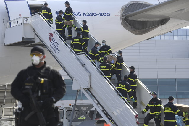 A police officer holds a gun as firefighters unload an airplane after its arrival at the Vaclav Havel Airport in Prague, Friday, March 20, 2020. The airplane brought medical aid and protective materials against coronavirus from China. (Photo by Michal Kamaryt/CTK via AP Photo)