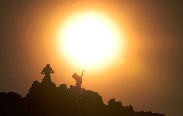 A couple celebrates summer solstice at a stone carved solstice marker at the Kokino megalithic observatory, on June 20, 2012. The 3,800-year-old observatory was discovered in 2001 in the northwestern town of Kumanovo, 70 km (43 miles) north of Skopje, and is ranked the fourth oldest observatory in the world, according to NASA. (Photo by Ognen Teofilovski/Reuters)