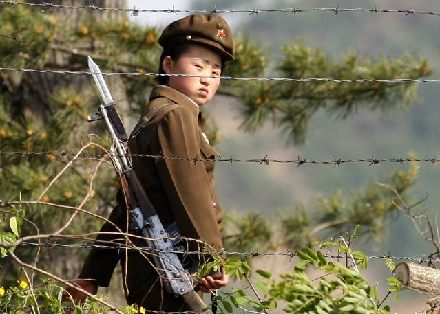 In this photo taken June 3, 2009, a female North Korean soldier looks out from behind a barbed-wire fence around a camp on the North Korean river banks across from Hekou, northeastern China's Liaoning province. North Korea's top court has convicted two U.S. journalists, and sentenced them to 12 years in labor prison, the country's state news agency reported Monday. (Photo by Ng Han Guan/AP Photo)