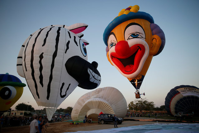 Hot air balloons are prepared before they take flight during a two-day international hot air balloon festival in Eshkol Park near the southern city of Netivot, Israel July 22, 2016. (Photo by Amir Cohen/Reuters)