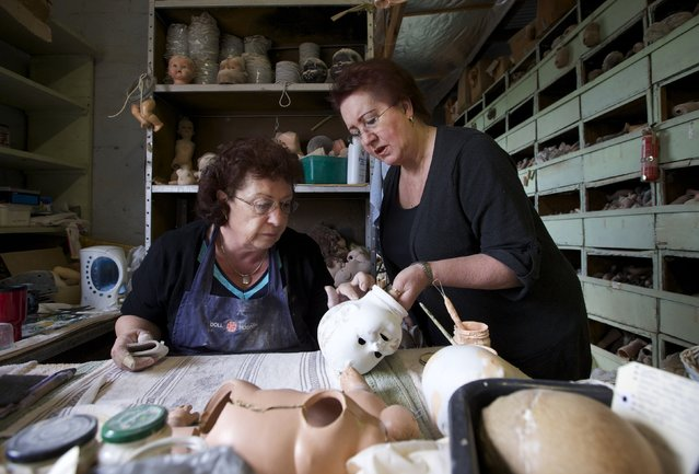 Doll restorers Gail Grainger (L) and Kerry Stuart inspect the head of a composition doll, made from compressed wood chip, in the workshop of Sydney's Doll Hospital, July 15, 2014. Photo by Jason Reed/Reuters)