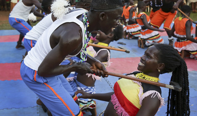 In this photo taken Tuesday, December 12, 2017, former child soldiers of the Lord's Resistance Army (LRA) and community members make a traditional Acholi dance performance at a music therapy pilot programme in Gulu, Uganda. (Photo by Adelle Kalakouti/AP Photo)