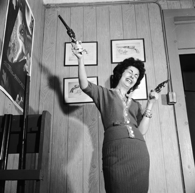 Lola Medina demonstrates the effects of handling a pair of pistols at Centre Firearms, a manufacturer of fake weapons for use in showbusiness, circa 1955. (Photo by Vecchio/Three Lions)
