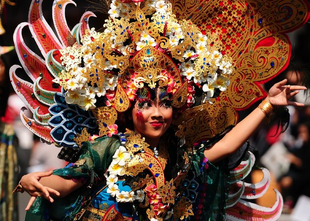 A model of  Bali Province performs in Wonderful Archipelago Carnival Indonesia during The 13th Jember Fashion Carnival  2014  on August 23, 2014 in Jember, Indonesia. The 13th Jember Fashion Carnival (JFC) 2014 theme is Triangle, Dynamic in Harmony and consists of ten parades which include Mahabharata, Tambora, Phoenix, Pine Forest, Apache, Borobudur, Flying Kite, Wild Deers, Stalagmite, and Chemistry. (Photo by Robertus Pudyanto/Getty Images)