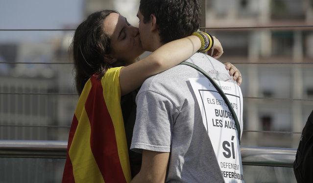 A couple kisses during a protest regarding the referendum in Barcelona, Spain, Thursday, September 28, 2017. Thousands of striking university students are marching through Barcelona to protest an intensifying central government crackdown on Sunday's planned independence referendum in Catalonia. (Photo by Manu Fernandez/AP Photo)