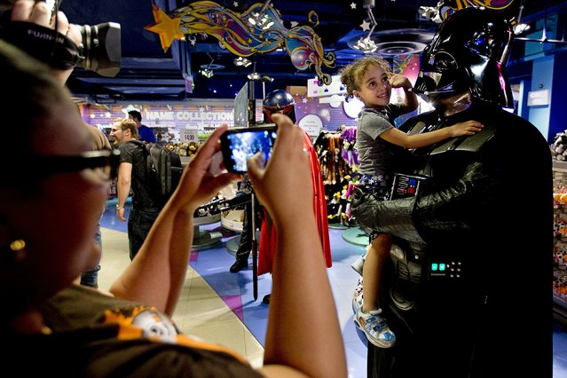 """A man dressed as Darth Vader from """"Star Wars"""" poses for a photo with a child as people arrive to purchase toys that went on sale at midnight in advance of the film """"Star Wars: The Force Awakens"""" in Times Square in the Manhattan borough of New York, September 4, 2015. (Photo by Carlo Allegri/Reuters)"""
