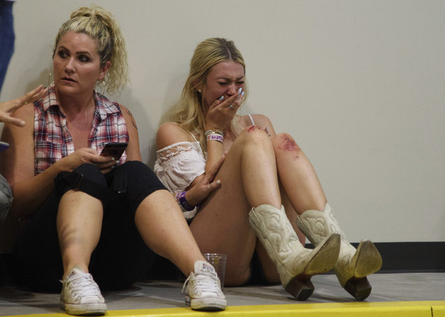 A woman cries while hiding inside the Sands Corporation plane hangar after a mass shooting in which dozens were killed at the Route 91 Harvest country festival on Sunday, October 1, 2017, in Las Vegas. (Photo by Al Powers/Invision/AP Photo)