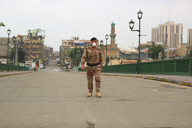 A federal police officer crosses an empty bridge over the Tigris River in Baghdad, Iraq, Wednesday, March 18, 2020. Iraq announced a weeklong curfew to help fight the spread of the virus. For most people, the virus causes only mild or moderate symptoms. For some it can cause more severe illness. (Photo by Hadi Mizban/AP Photo)