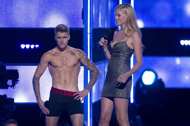 """Singer Justin Bieber (L) takes his shirt off as he and model Lara Stone introduce an act during the """"Fashion Rocks 2014"""" concert in the Brooklyn borough of New York September 9, 2014. (Photo by Carlo Allegri/Reuters)"""