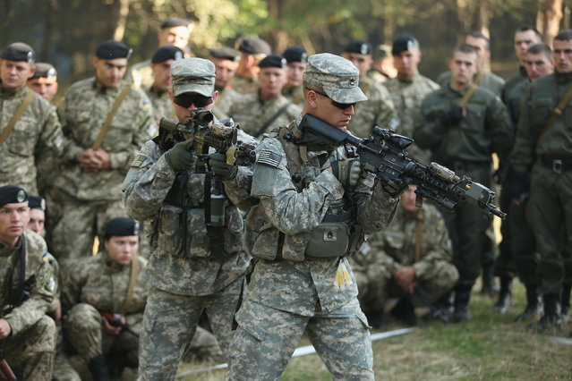 "Members of the U.S. Army 173rd Airborne Brigade demonstrate urban warfare techniques as Ukrainian soldiers look on on the second day of the ""Rapid Trident"" NATO military exercises on September 16, 2014 near Yavorov, Ukraine. (Photo by Sean Gallup/Getty Images)"