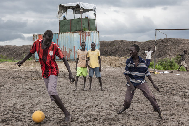 Boys play soccer in front of a UN Peacekeepers outpost at the Protection of Civilians (POC) site at the United Nations Mission in South Sudan (UNMISS) compound in Malakal, South Sudan on Wednesday, July 13, 2016. (Photo by Jane Hahn/The Washington Post)