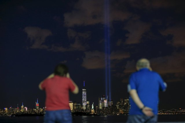 People take pictures of the Tribute in Light while it is illuminated next to the Statue of Liberty (C), One World Trade Center and the Empire State Building during events marking the 14th anniversary of the 9/11 attacks on the World Trade Center in New York September 11, 2015. (Photo by Eduardo Munoz/Reuters)