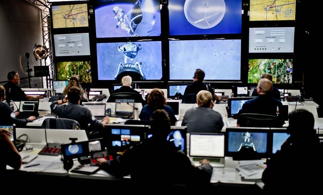 Crew members at mission control watch the jump. (Photo by Joerg Mitter/Red Bull)