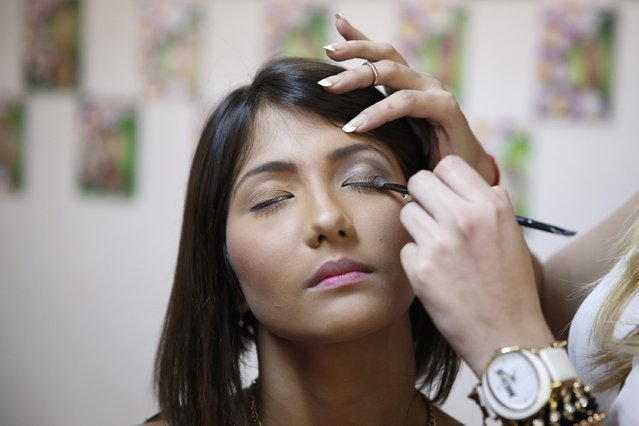 A teacher demonstrates makeup techniques on the face of a student, during a class at a modelling academy in Caracas September 20, 2014. (Photo by Carlos Garcia Rawlins/Reuters)