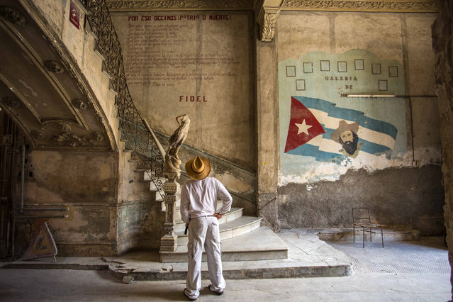 """A tourist looks at quote by Cuban Revolution leader Fidel Castro explaining in Spanish, """"Why we say homeland or death"""", on a wall at the entrance of a landmark private restaurant  in Havana, Cuba, Thursday, July 28, 2016. After a decade out of the public eye, Fidel Castro has surged back in the run-up to his birthday next month as the inspiration for Cubans who want to maintain Communist orthodoxy in the face of mounting pressures to loosen control. (Photo by Desmond Boylan/AP Photo)"""