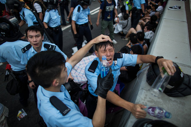 Police clash with demonstrators during a protest near the central government offices in Hong Kong, China, on Sunday, September 28, 2014. Pro-democracy protesters kick-started their campaign to occupy central Hong Kong after police clashed with students, demanding that China withdraws proposals to control the city's elections. (Photo by Lam Yik Fei/Bloomberg)