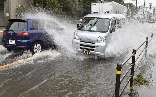 Vehicles advance through a flooded street in Chiba, near Tokyo, Monday, October 6, 2014. A powerful typhoon made landfall in central Japan Monday morning after washing three American airmen in Okinawa out to sea the previous day, killing at least one. Bullet train service was suspended between Tokyo and Osaka because of heavy rain, and more than 600 flights were canceled at Tokyo's Haneda Airport. (Photo by AP Photo/Kyodo News)