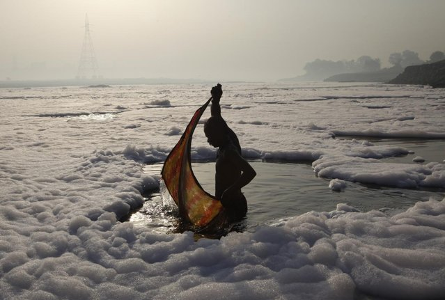 A Hindu devotee wraps his cloth after a ritual dip in the polluted Yamuna river in New Delhi March 21, 2010. (Photo by Danish Siddiqui/Reuters)
