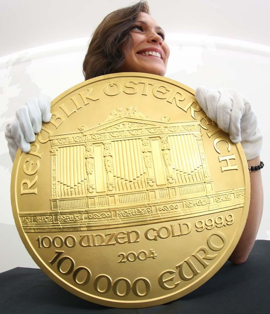 "A woman presents Europe's biggest gold coin during an exhibition at the Pro Aurum trade house in Hamburg, northern Germany. The so-called ""Big Phil"" made after the model of an Austrian coin weighs around 31 kilograms and is worth more than 1.3 million euros or 1.7 million US dollars. ""Big Phil"" is on display at Pro Aurum until November 17, 2012. (Photo by Christian Charisius)"