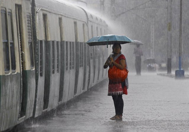A woman holds an umbrella while waiting to board a train during a heavy rain shower at a railway station in Kolkata September 20, 2014. Weather officials expect rains to weaken from this weekend as the June-September monsoon season begins a delayed retreat. (Photo by Rupak De Chowdhuri/Reuters)