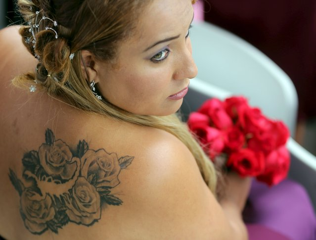 A bride is pictured with a tattoo of roses during a mass wedding ceremony at Arena Corinthians soccer stadium in Sao Paulo, Brazil, September 26, 2015. (Photo by Paulo Whitaker/Reuters)