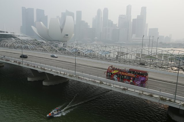 A tourist bus passes the skyline of the central business district shrouded by haze in Singapore September 29, 2015. (Photo by Edgar Su/Reuters)