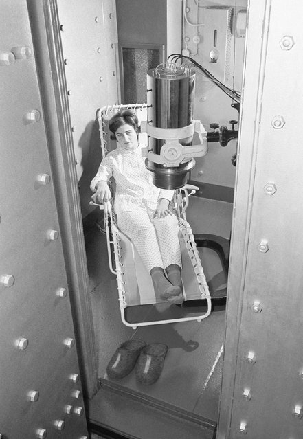 Miss Gisela Kosswig, a technical assistant at the Max-Plank institute for Biophysics in Frankfurt, sits in the patient's chair inside the steel chamber of the new Gamma-Ray spectrometer at the institute in Frankfurt, Germany on January 25, 1961. Over her is the spectrometer's head. The patient wear pyjamas specially made and dry-cleaned by the institute to ensure complete freedom from radioactive materials. The spectrometer measures and analyses the amount, kind and exact location of radio-active substances in the human body. It cost about £31,500 to build. (Photo by AP Photo)