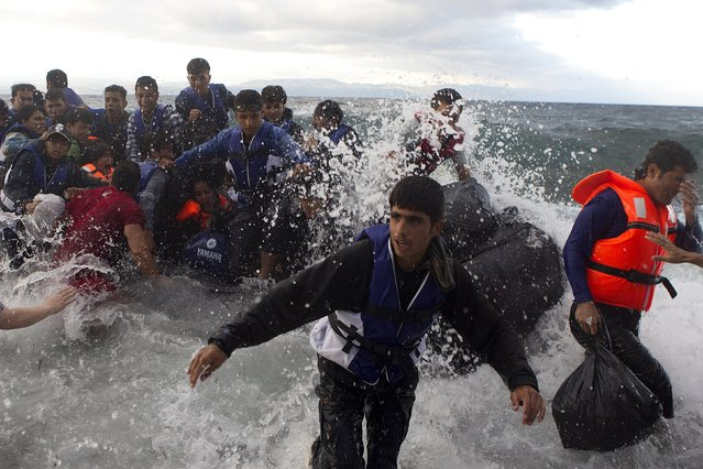 Refugees and migrants struggle to jump off an overcrowded dinghy on the Greek island of Lesbos, after crossing in rough seas from the Turkish coast, October 2, 2015. (Photo by Dimitris Michalakis/Reuters)