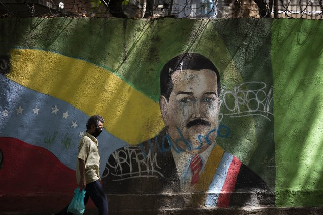 A man wearing a face mask amid the COVID-19 pandemic passes a mural of Venezuelan President Nicolas Maduro in Caracas, Venezuela, Wednesday, July 22, 2020. Analysts say that in recent months the pandemic has helped suck away the opposition's scanty momentum and bolster Maduro's already strong hand. (Photo by Ariana Cubillos/AP Photo)