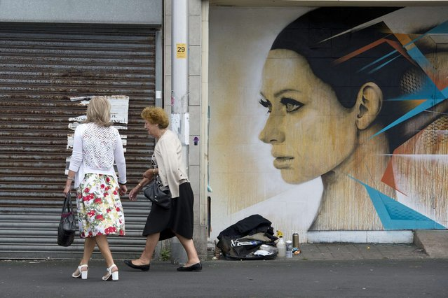 "Women walk past a piece of street art created as part of the ""Sand Sea & Spray"" Urban Art Festival in Blackpool, north west England on July 11, 2015. (Photo by Oli Scarff/AFP Photo)"