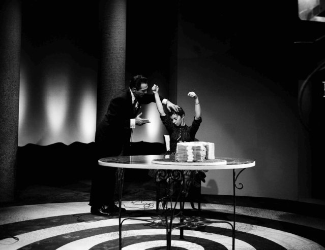 Arthur Ellen, a professional hypnotist, puts a 19-year-old student, Pat Morris, under hypnosis as she tried for the $100,000 prize on the Truth Or Consequences TV show, in Hollywood, October 7, 1955. She is falling into a deep trance as Ellen says the words Nena, Zena, Rena. Then he told her she was unable to rise and pick up the $100,000 in bills, lying on the table before her. (Photo by David F. Smith/AP Photo)