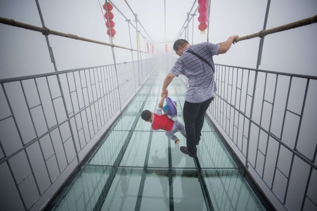 A Chinese tourist holds onto his son as they walk across a glass-bottomed suspension bridge in the Shinuizhai mountains in Pingjang county, Hunan province some 150 kilometers from Changsha on October 7, 2015. (Photo by Johannes Eisele/AFP Photo)