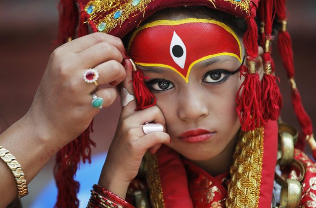 A Nepalese mother applies make up to her daughter dressed as the living goddess Kumari as they wait for Kumari puja to start at Hanuman Dhoka temple, in Kathmandu, Nepal, Wednesday, September 14, 2016. Girls under the age of nine gathered for the Kumari puja, a tradition of worshiping young prepubescent girls as manifestations of the divine female energy. The ritual holds a strong religious significance in the Newar community that seeks divine blessings to save small girls from diseases and bad luck in the years to come. (Photo by Niranjan Shrestha/AP Photo)