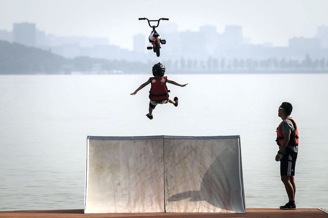 A boy cycling enthusiast performs a stunt with a bicycle before falling into the East Lake in on August 22, 2020 in Wuhan, Hubei province, China. This activity, which requires participants to ride their bikes and jump into the lake, attracts many extreme cycling enthusiasts from the city.The event was held in 2010 and is the ten time this year. There have been no recorded cases of community transmission in Wuhan since May. Life in Wuhan returned to normal. (Photo by Getty Images/China Stringer Network)