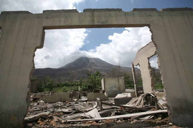In this October 17, 2014, photo, Mount Sinabung is framed by a crumbling building in the abandoned village of Simacem village, North Sumatra, Indonesia. The village was abandoned after its people were evacuated following the eruption of the volcano. Sinabung, among about 130 active volcanoes in Indonesia, has sporadically erupted since 2010 after being dormant for 400 years. (Photo by Binsar Bakkara/AP Photo)