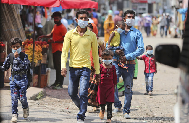 Indians wearing face masks as a precaution against the coronavirus walk at a bus station in Jammu, India, Friday, September 11, 2020. By early May, 6.4 million people in India were likely infected by the coronavirus, said a study released Thursday, Sept. 10, by Indian scientists from the Indian Council of Medical Research, India's apex medical research body and published in their in-house medical journal. At the time, India had detected around 35,000 cases and over a thousand deaths. But the results of India's first nationwide study of prevailing infections in the country found that for every confirmed case that detected in May, authorities were missing between 82 and 130 infections. The study tested 28,000 people for proteins produced in response to the virus in the villages and towns across 70 districts in 21 Indian states between May 11 to June 14. (Photo by Channi Anand/AP Photo)