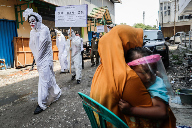 """Officials dressed up as """"pocong"""" or shroud ghosts march during a COVID-19 awareness campaign at a market in Tangerang, outskirt of Jakarta, Indonesia, 16 September 2020. Indonesia has recorded over 200,000 cases of COVID-19 since the pandemic started, with nearly 9,000 deaths, the highest number in Southeast Asia. (Photo by Mast Irham/EPA/EFE)"""
