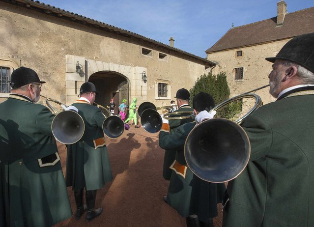 Hunters with horns greet competitors who run during the Marathon International du Beaujolais race at the castle of Corcelles, November 22, 2014. (Photo by Robert Pratta/Reuters)