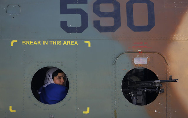 An Afghan woman looks out from a helicopter window at the International Airport in Kabul March 7, 2013. Afghan women take a tour around Kabul to mark International Women's Day. (Photo by Mohammad Ismail/Reuters)