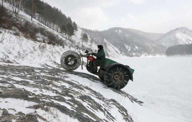 "Alexander Yushkov, 49, a boiler room operator in a local mining company, drives his self-made three-wheeled cross-country vehicle called ""Bolivar"" near the frozen Mana river in a remote taiga area, some 60 km (37 miles) southeast of Russia's Siberian city of Krasnoyarsk March 11, 2013. Yushkov created the vehicle for off-road travel across the taiga through all possible weather conditions by modifying and reconstructing a 1971 Soviet made ""Izh Planeta"" motorcycle. (Photo by Ilya Naymushin/Reuters)"