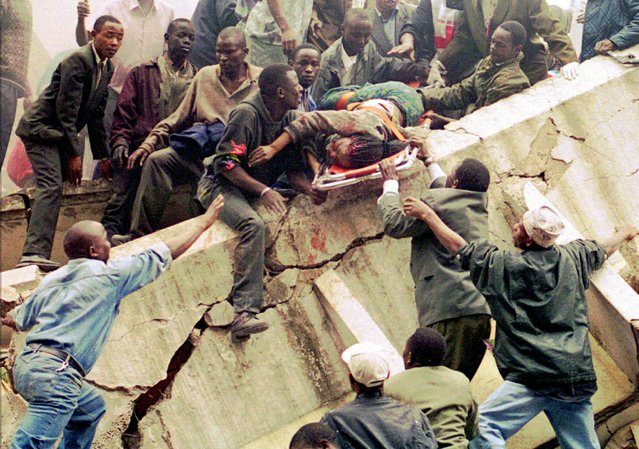 Rescue workers carry Susan Francisca Murianki, a U.S. Embassy office worker, over the rubble of a collapsed building next to the embassy, Friday, August 7, 1998 in Nairobi, Kenya. Terrorist bombs exploded minutes apart outside the U.S. embassies in the Kenyan and Tanzanian capitals Friday. Americans were among the dead, and the U.S. ambassador to Kenya was injured, the State Department said. More than 40 people were killed and 1,000 wounded in Nairobi alone. (Photo by Khalil Senosi/AP Photo)