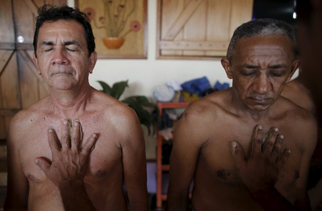 Prisoners Helio Steves (L), 57, and Epifacio Soares, 62, are covered in clay by fellow inmates during a therapy session as part of the ACUDA programme at a complex of ten prisons in Porto Velho, Rondonia State, Brazil, August 28, 2015. (Photo by Nacho Doce/Reuters)